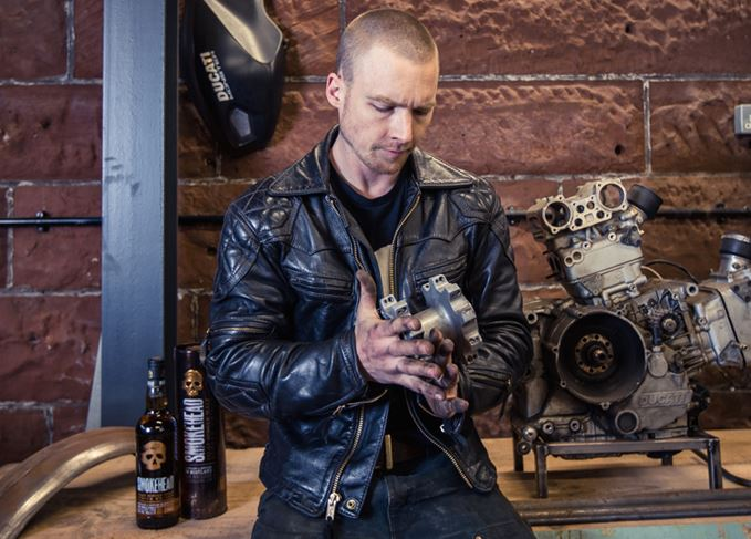 Tyler Lunceford with Smokehead whisky in motorbike workshop