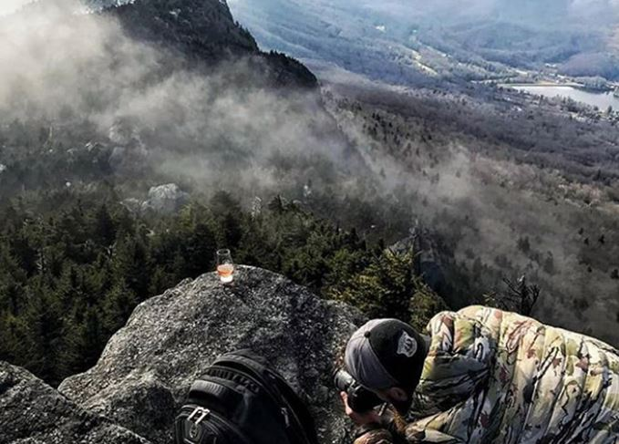 Instagram influencer Whisky with a View (Nathan Woodruff) takes a photo from a mountain summit.
