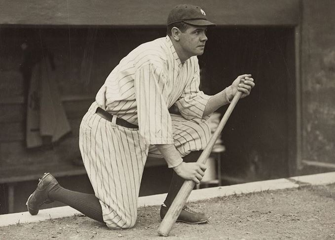 Babe Ruth kneeling with bat