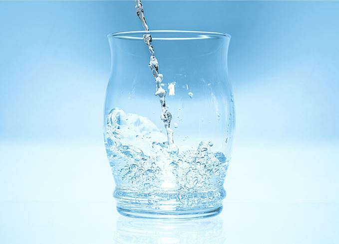 Water droplets falling into a glass