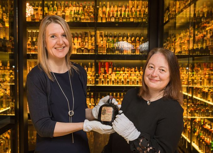 The Scotch Whisky Experience's Susan Morrison and Diageo archivist Christine McCafferty, with a Ballantine's from the Claive Vidiz Collection
