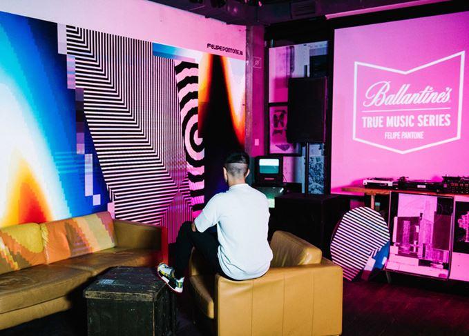 Felipe Pantone examining art piece with Ballantines logo