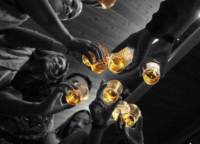 Friends toasting with whisky glasses
